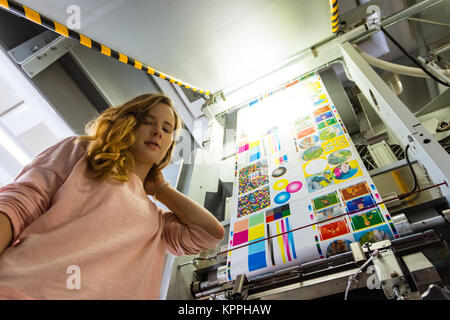 Young Female Girl Engineer Printing Specialist Gravure Intaglio Printing Industrial Machine Packaging Newspaper - Stock Photo