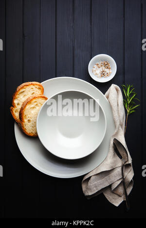 serving soup. Empty Plates and bread. on a dark background. clean linen napkin - Stock Photo