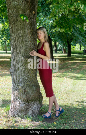 Blonde woman hugging a tree in park. Young girl in a red dress resting in nature, leaned against a tree. In the - Stock Photo