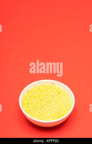 cornmeal a bowl on a colored background - Stock Photo