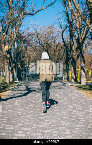 Sports woman runs through the park in the autumn morning, the view from the back - Stock Photo