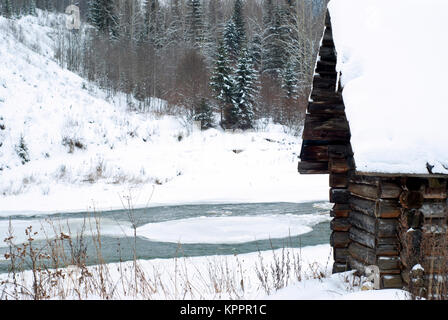 fragment of an old log hunting cabin on the river bank in a winter landscape - Stock Photo