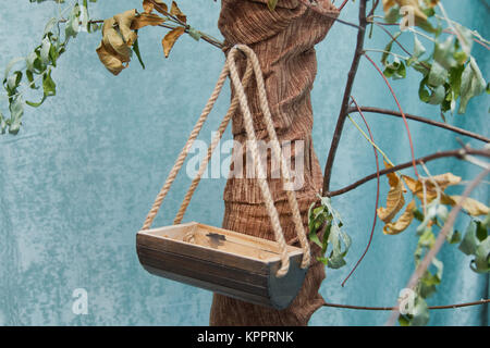 Bird's nest on the tree Hand painted little birdhouse hanging on branches of tree - Stock Photo