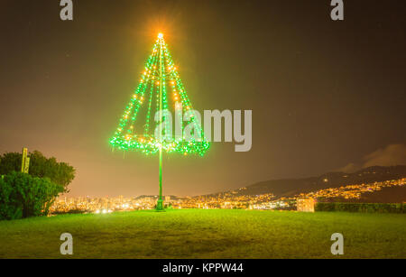 A large, outdoor, metal Christmas tree brightly illuminated with green and gold Christmas lights, at night time - Stock Photo