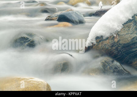 Close-up of the current between the stones of a mountain stream, photographed with a long exposure - Stock Photo