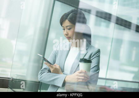 Businesswoman use of mobile phone inside office building - Stock Photo