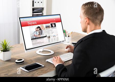 Businessman Reading News On Computer - Stock Photo