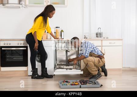 Repairing Dishwasher In Kitchen - Stock Photo