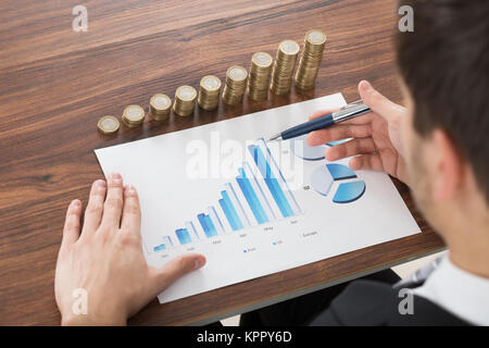 Businessman Analyzing Financial Graph - Stock Photo