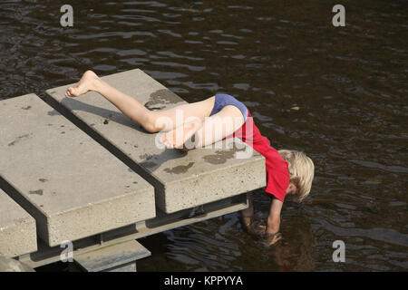 Germnay, Bergisches Land region, Muengsten, boy lying on a landing stage at the river Wupper.  Deutschland, Bergisches - Stock Photo
