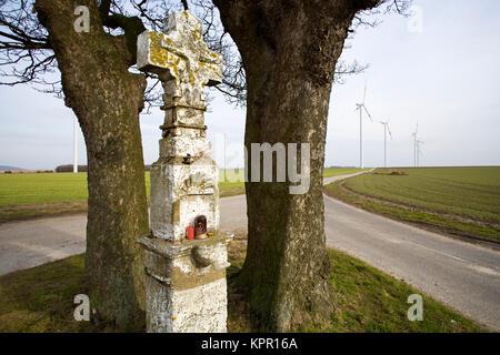Europe, Germany, roadside cross near Bedburg, in the background wind power plants.   Europa, Deutschland, Wegkreuz - Stock Photo
