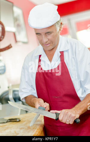 Butcher sharpening a knife - Stock Photo