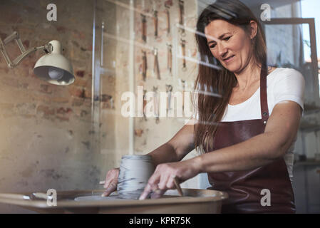 Female artisan creatively shaping a piece of clay turning on a pottery wheel while working in her ceramic studio - Stock Photo