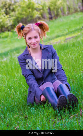 Cheerful young girl sitting on the green grass - Stock Photo