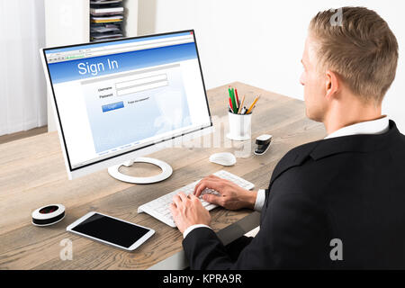 Businessman Signing Into A Website On Computer - Stock Photo