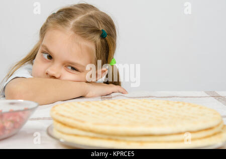 The girl at the kitchen table laid her head on his hand, and with an appetite for looking at cakes in front of her - Stock Photo