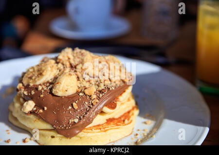 Pancakes with chocolate sauce on a white plate. Closeup view and blurred coffee shop background. - Stock Photo