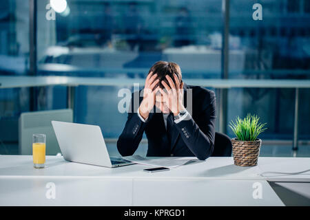 Stressed businessman having problems and headache at work - Stock Photo