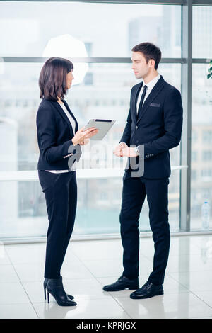 Businesswoman with male colleague using tablet computer - Stock Photo