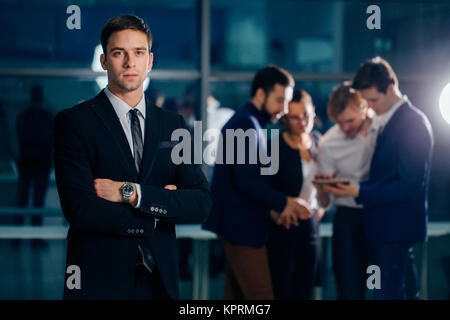small business owner standing with crossed arms with employee in background - Stock Photo