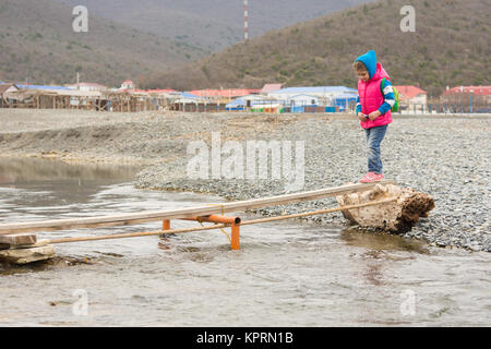 Five-year girl timidly comes on board thrown across the stream - Stock Photo