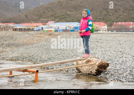 A five-year girl is undecided at the end of the plank thrown across a stream - Stock Photo