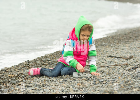 Seven-year girl sitting on a pebble beach in the warm clothing and with enthusiasm plays with stones - Stock Photo