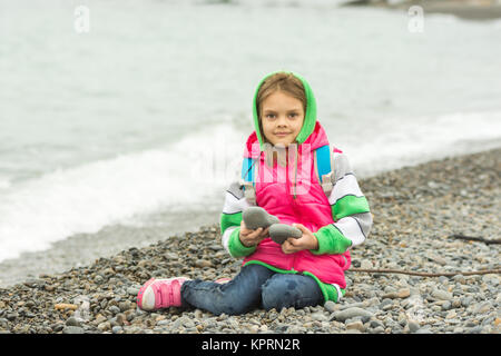 Seven-year girl sitting on a pebble beach in the warm clothes and looks in the frame - Stock Photo