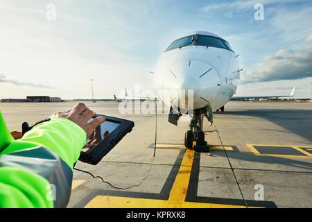 Modern technology at the airport. Member of the ground staff preparing the passenger airplane before flight. - Stock Photo