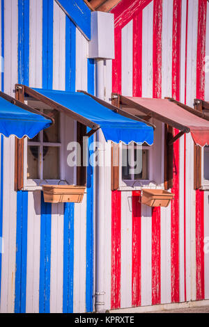 Colorful striped fishermen's houses in blue and red, Costa Nova, Aveiro, Portugal - Stock Photo