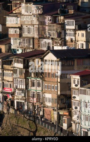 Tiered houses and ramshackle buildings on steep hillside in Shimla, India - Stock Photo