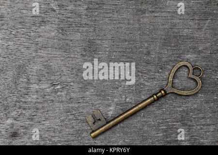 golden heart shaped vintage key on grunge wooden background - Stock Photo