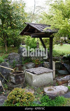 Traditional ancient stone well in japanese garden - Stock Photo