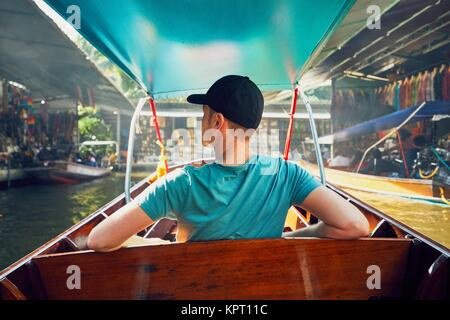 Young man (traveler) on the boat. Traditional floating market Damnoen Saduak in Ratchaburi near Bangkok, Thailand. - Stock Photo