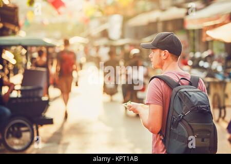Young man (tourist)  with backpack walking to the night market buying tasty sweet food. Busy street full of restaurants, - Stock Photo