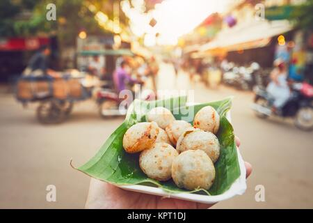 Hand of man holding bowl with sweet coconut food. Busy street full of restaurants, bars and shops - Siem Reap, Cambodia - Stock Photo