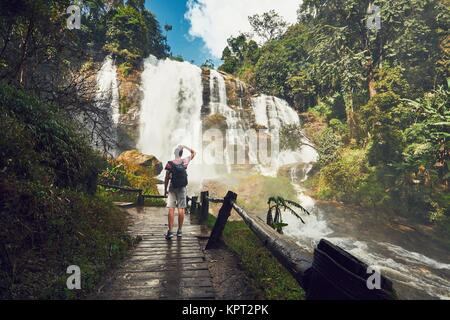Young man (traveler) standing near Wachirathan waterfall in tropical rainforest. Chiang Mai Province, Thailand - Stock Photo