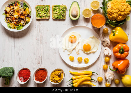 Healthy food for Breakfast. Fried eggs, vegan avocado sandwiches, veggies salad, carrot fresh juice and Different - Stock Photo