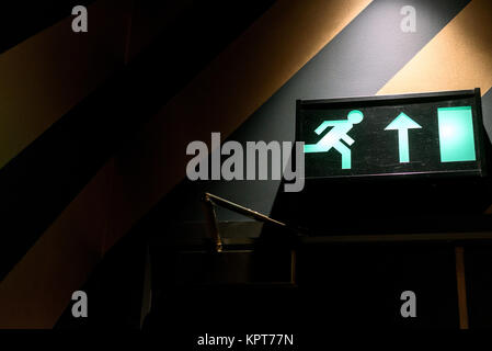 Emergency exit sign in green neon and internal interior light with copyspace area - Stock Photo