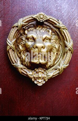 Single golden coloured brass lions head door knocker and vintage antique wooden door in dark burgundy & Brass lions head door knocker on a red door in the old town Mdina ...