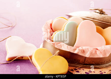 Colorful glazed heart shaped cookies with fondant filling served in an old oval tin on a lilac background with copy - Stock Photo