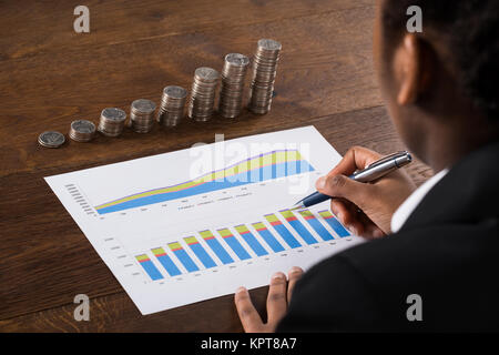 Businesswoman Analyzing Financial Graph With Coins On Desk - Stock Photo