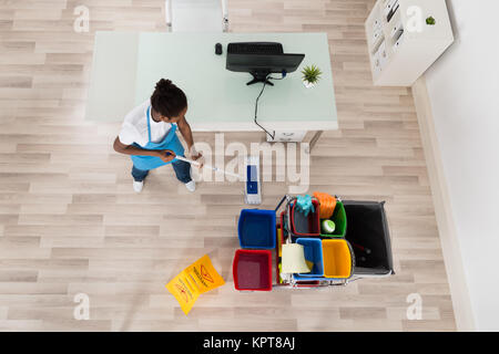 Young Female Janitor Mopping Wooden Floor - Stock Photo