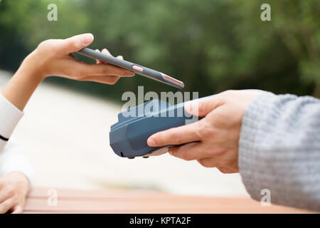 Woman pay the bill with mobile phone - Stock Photo