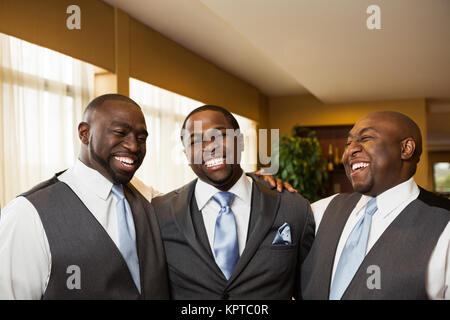 Groom and groomsmen smiling at a wedding. - Stock Photo