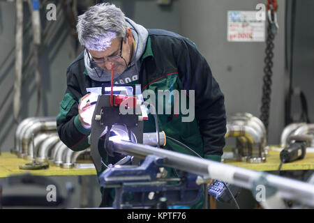 Industrial operator setting  computer controlled process of orbital welding machine in  stainless steel pipes manufacturing - Stock Photo