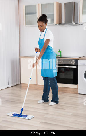 Female Janitor Mopping Floor In Kitchen - Stock Photo