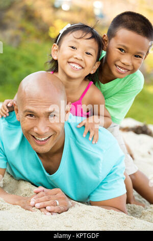 Father playing with his kids on the beach. - Stock Photo