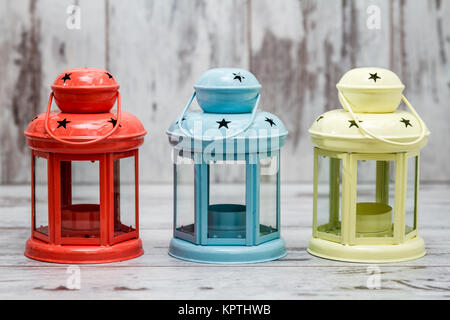 Colorful Candle Holders on White Wooden Background - Stock Photo