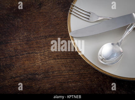 Close up Spoon, Fork and Knife Tied on White Dish with Empty Tag, on Wooden Table with Text Space. - Stock Photo
